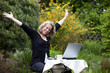 jubelnde hübsche blonde Frau mit Laptop im Garten