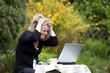 hübsche Frau mit Laptop im Grünen rauft sich die Haare