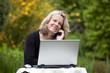 hübsche blonde Frau mit Laptop telefoniert mit Mobiltelefon - 22894742