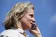 hübsche blonde Frau mit Mobiltelefon im Freien