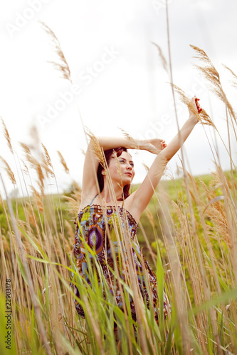beautiful young model dancing through the reed in summer