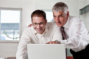 Geschaeftsleute betrachten einen Laptop