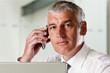 Leinwanddruck Bild - Geschäftsmann arbeitet am Laptop und telefoniert