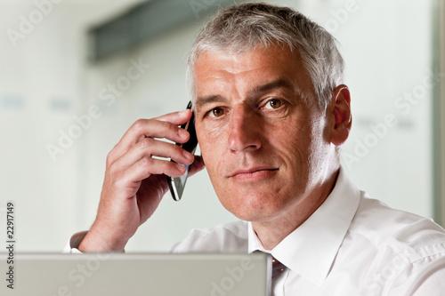 Leinwanddruck Bild Geschäftsmann arbeitet am Laptop und telefoniert