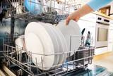 female hands loading dishes to the dishwasher poster
