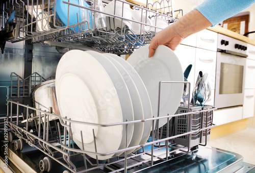 canvas print picture female hands loading dishes to the dishwasher