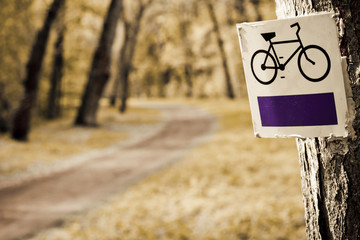Bike sign with bicycle path in background. Park in autumn.