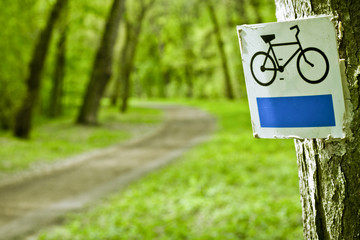 Bike sign with bicycle path in background. Park.
