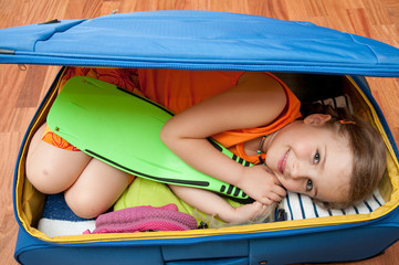 Little girl  ready for travel into suitcase