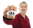 Mature man holds a white nest egg with IRA on it.