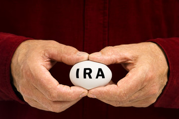 Man holds white nest egg with IRA written on it