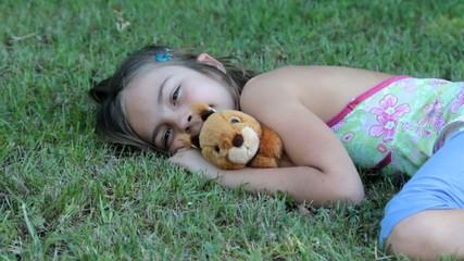 allongée dans l'herbe avec la peluche écureuil