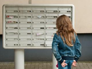 Kind vor Briefkasten
