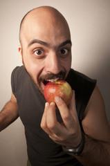 uomo buffo che mangia una mela