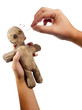 hands holding creepy voodoo doll with needles isolated on white