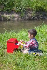 河原でピアノを弾く幼児