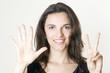 Hübsche Frau zeigt mit sieben Fingern die Zahl 7 an