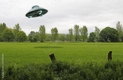 Foto op Canvas UFO UFO über grüner Wiese