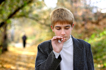 problem teenager smoking cigarette in the park