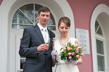 Bride and groom standing near registry office