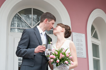 Bride and groom standing near registry office with glasses