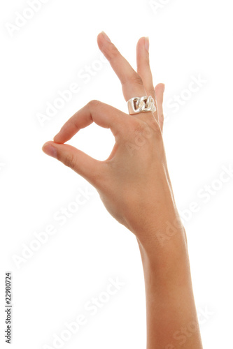 Woman's hand making OK sign over white background