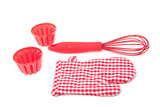 two cake molds with a  whisk and a checkered kitchen glove isola