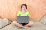 Girl lying on sofa in livingroom  with laptop poster