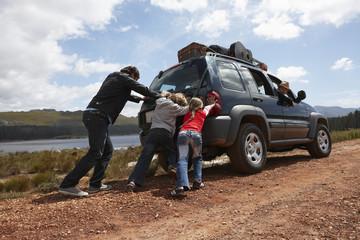 Family pushing a car
