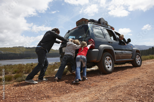 Family pushing a car