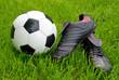 Fußballschuhe und Ball auf Rasen
