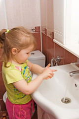 The little girl washes hands