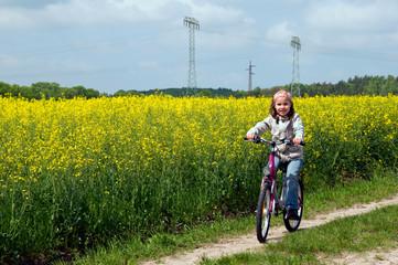 Mädchen fährt Rad am Rapsfeld