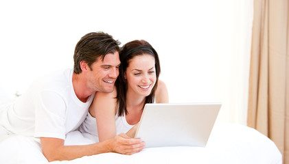 Cheerful couple using a computer lying on their bed