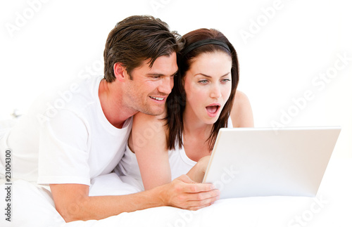 Surprised couple using a computer lying on their bed