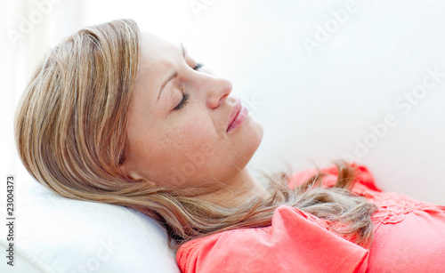 Portrait of an attractive woman sleeping lying on a sofa - 23004373