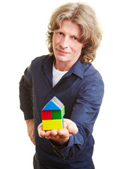 Mann mit Baustein-Haus