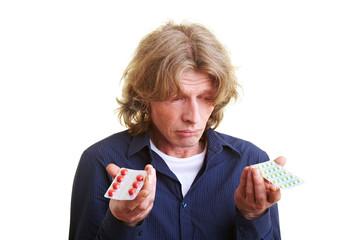Mann vergleicht Medikamente