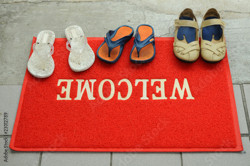 Photo: Pairs Of Shoes At A Red Welcome Mat