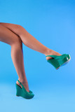 Slender beautiful female legs in green sandals poster