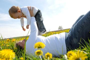 Mutter mit Kleinkind im Löwenzahnfeld