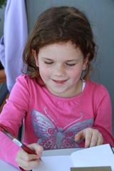 Lächelndes Mädchen beim Schreiben