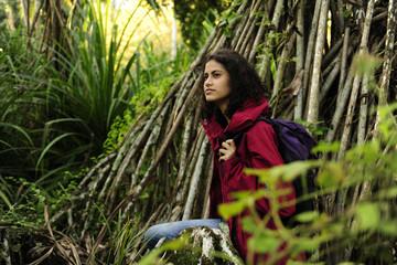 ecotourism: female  hiker exploring wilderness of rainforest
