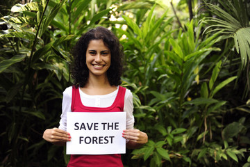environment conservation: woman holding a save the forest sign