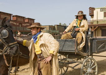 Cowboys waiting by a wagon