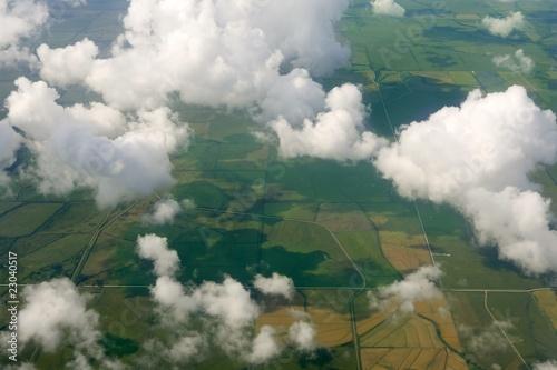 Aircraft bird view of green fields white clouds