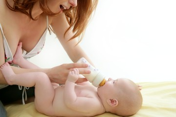nude blond baby playing mother hands