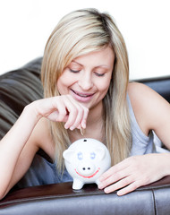Radiant woman using a piggybank