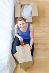 Smiling woman closing a box