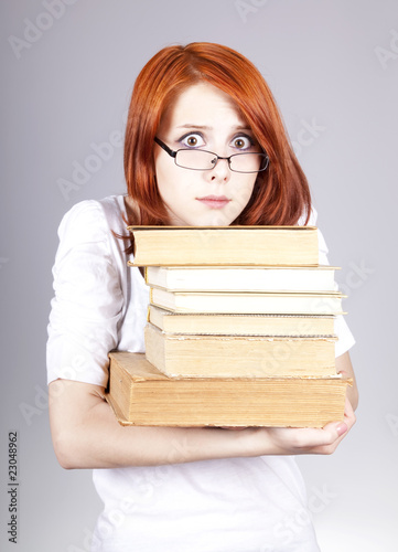 Red-haired businesswoman keep books in hand.